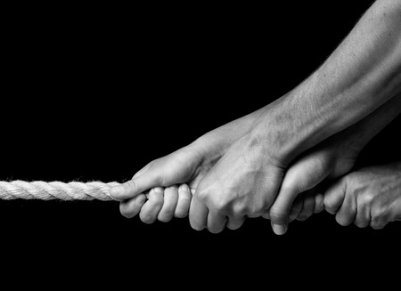 four hands pulling on a rope in same direction, black and white photo