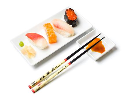 mussle: nigiri sushi variation with wasabi, ginger, chopsticks, caviar, tuna, heart-mussle on rectangular plates, isolated on white Stock Photo