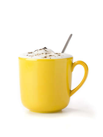 yellow mug filled with cappucino, with cocoa powder on froth, spoon inside, isolated on white photo