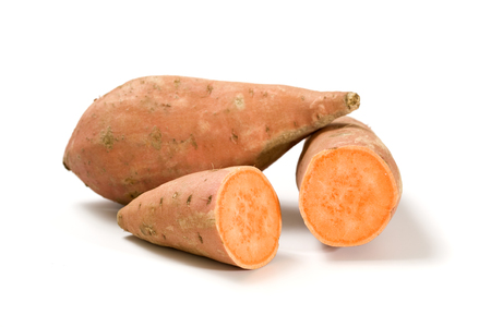 whole and halved sweet potatoes isolated on white photo
