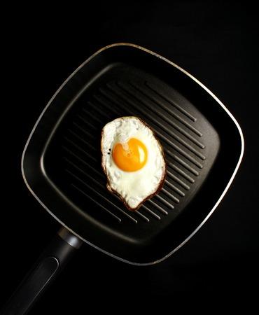fired egg: fired egg in pan, black background Stock Photo