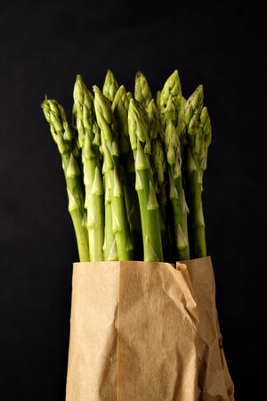 green asparagus in a brown paper bag, dark background Stock Photo