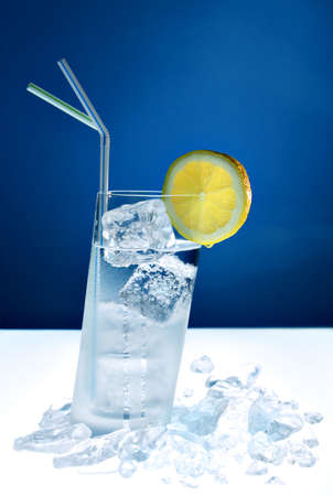 longdrink: slanted longdrink glass filled with clear liquid and ice cubes, with straws and lemon slice