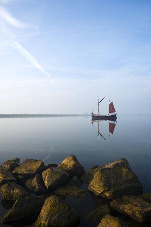 ijsselmeer: small fisherboat at lonely bay of ijsselmeer, fully reflected