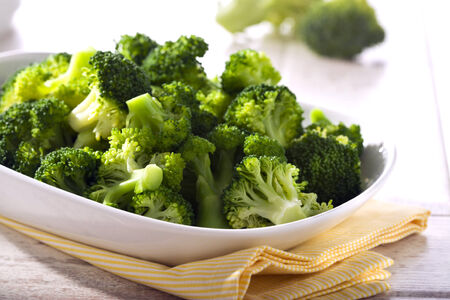 prepared broccoli in a bowl on table photo