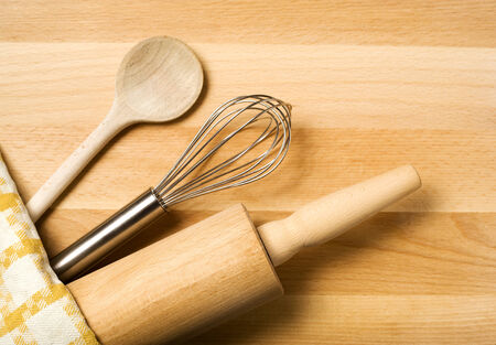 cooking utensils: spoon, whisker, rolling pin, towel on wooden board Stock Photo