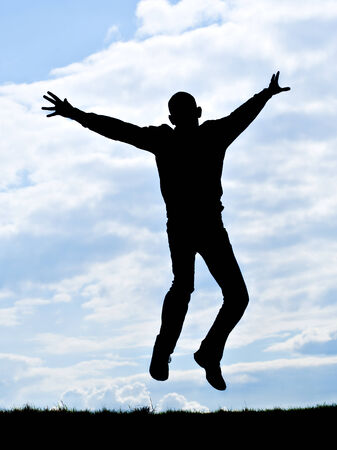 silhouette of young man jumping for joy