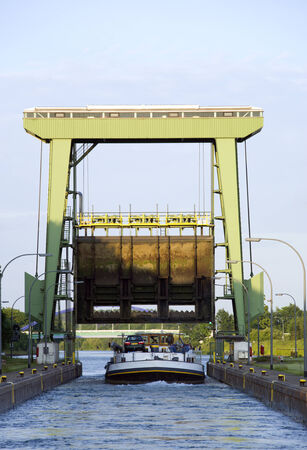 canal lock: smaller cargo ship leaving a canal lock Stock Photo
