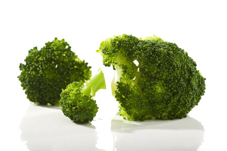 florets: three boiled broccoli florets on white surface Stock Photo