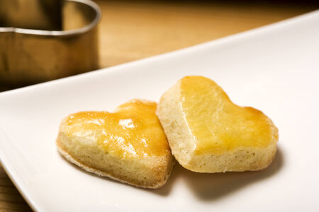 hart shaped: two hart shaped cookies on plate, cookie cutter in background