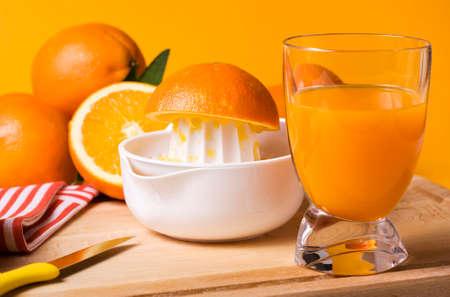 juice squeezer: kitchen scenery - glass of fresh orange juice, citrus squeezer, knife and fruit Stock Photo