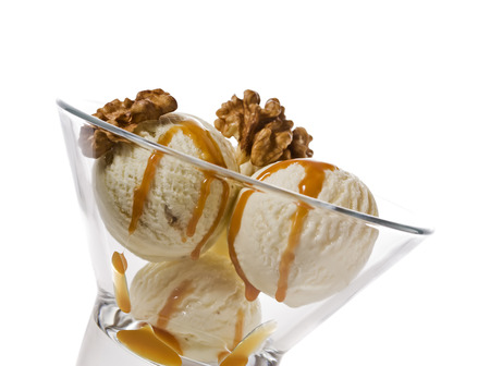 three balls of ice cream with walnuts and maple syrup topping in glass bowl, isolated on white Stock Photo