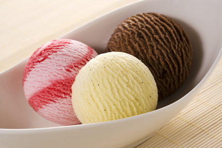 tilted view: scoops of icecream - chocolate, vanilla, strawberry - in a bowl, tilted view