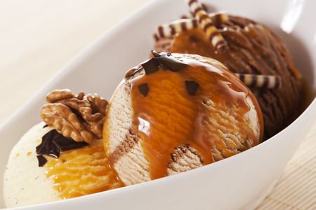 chocolate ice cream: Three Scoops of Ice Cream with walnuts, chocolate chips and caramel topping Stock Photo