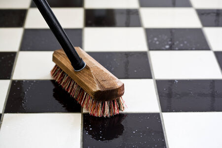 fregando: fregar un suelo de baldosas Foto de archivo