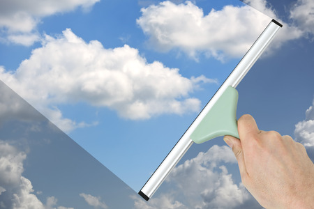 squeegee: hand cleaning tiled wall with a squeegee Stock Photo