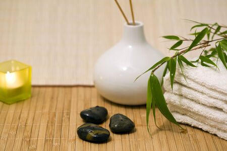 incense sticks: candle, incense sticks in vase, towels, hot stones, bamboo branch on bamboo mat Stock Photo