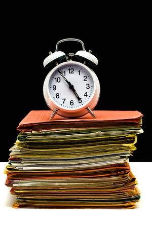 alarm clock, hands on six minutes to five oclock on a stack of full file folders photo