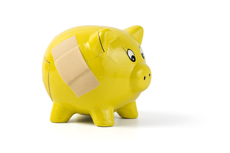repaired: cracked yellow piggy bank repaired with bandaid, isolated on white