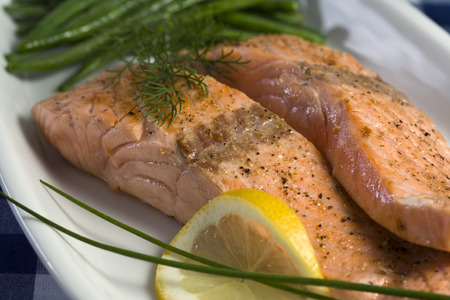 broiled: tender fillets of broiled salmon garnished with chives, dill and lemon slice Stock Photo