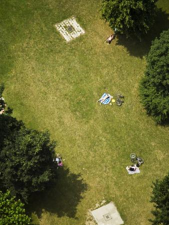 Varias personas que toman el sol en el césped en el parque, opinión de los pájaros Foto de archivo - 29446266