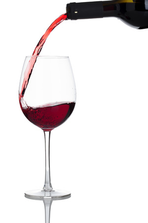 red wine is poured into a glass, isolated on white background
