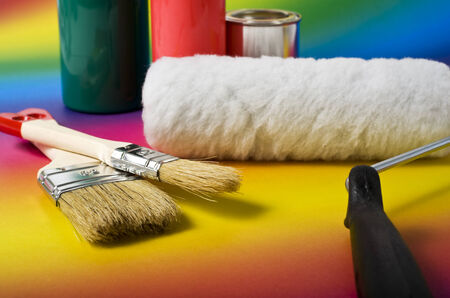 paintroller: paintbrushes, paintroller, color bottles and can on rainbow background Stock Photo