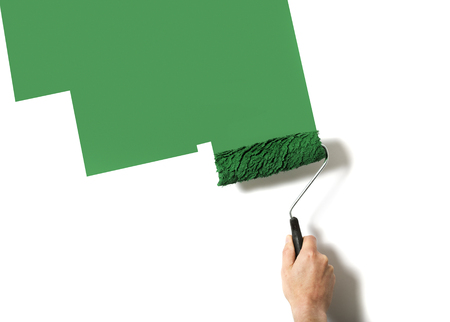paintroller: hand with paintroller painting a wall green Stock Photo