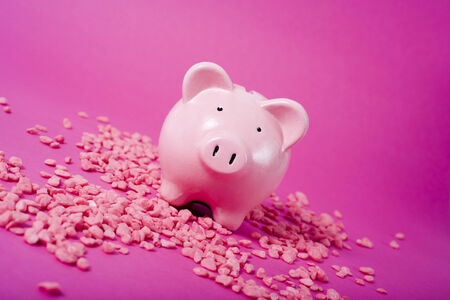 tilted view: piggy bank on magenta colored background, with pink gravel, tilted view Stock Photo