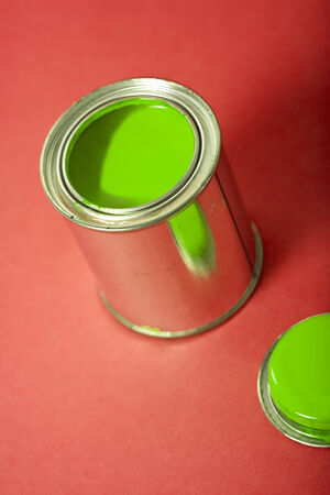 tilted view: open can of green varnish on red background, tilted view Stock Photo