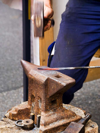 forging: smith forging hot metal on the anvil, hammer is motion-blurred