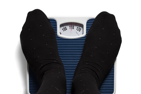 feet of man in black socks on bathroom scale showing 110 kilogram