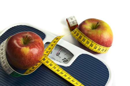 bathroom scale: stwo apples and a tape meaure on bathroom scales