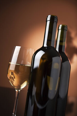 tilted view: glass of white wine and two bottles, tilted view