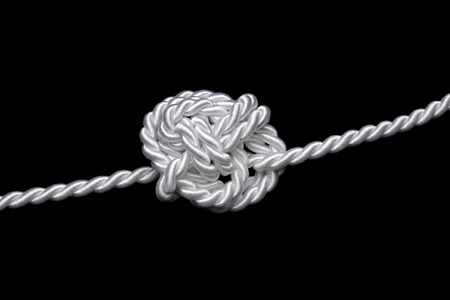 unsolvable: white cordon bound to a difficult knot, black background Stock Photo