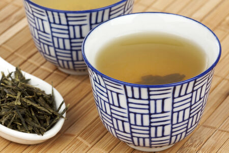 alternative medicine: two china cups of green tea, tea leaves on a spoon Stock Photo