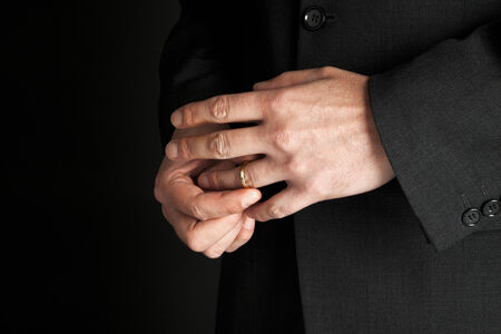 hombre maduro que saca su anillo de bodas de oro, primer plano en las manos