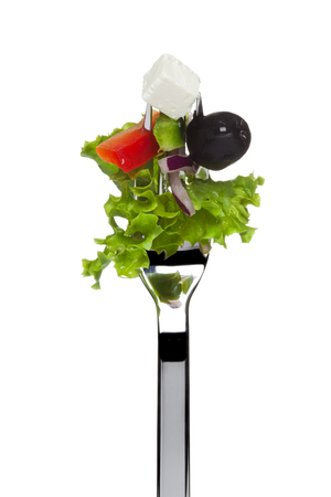 tine: fresh greek salad consisting of lollo bionda lettuce, black olive, sheep cheese, red onion and tomato sticked on fork, isolated on white Stock Photo