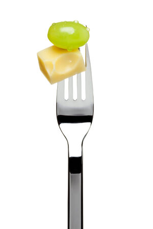 emmental: piece of emmental cheese and green grape sticked on a fork