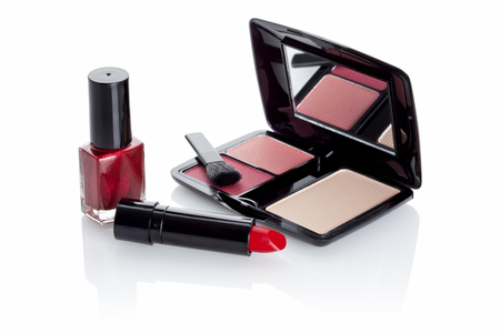 attractiveness: red nail varnish, lipstick and make-up in case with mirror isolated in white Stock Photo