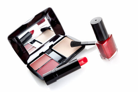 tilted view: make-up in case with mirror, red lipstick and nail varnish on white background, tilted view