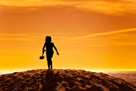silhouette of little girl with shovel on a sand hill at the beach in sunset photo