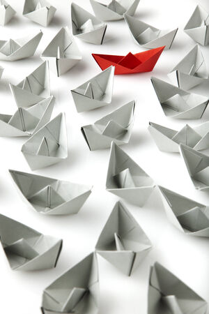 single red paper boat between lots of gray paper boats photo