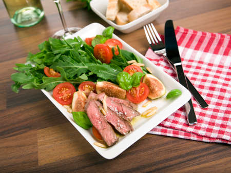 tilted view: salad with arugula, fried beef strips, tomatoes, figs and pine seeds, tilted view Stock Photo