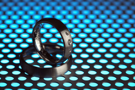 titanium: silver or titanium wedding rings on perforated sheet metal in blue light