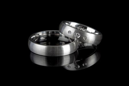 anillo de boda: plata o titanio anillos de boda refleja en el fondo negro Foto de archivo