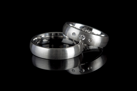 silver or titanium wedding rings reflected on black background Stock Photo