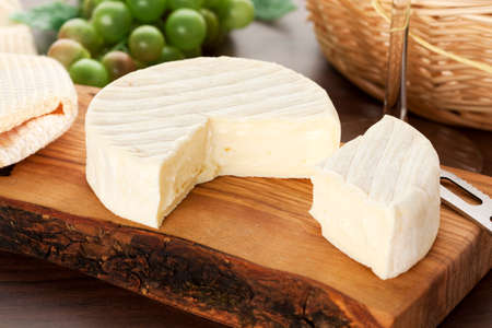 cheese platter: camembert cheese on wooden board with knife, wineglass bread basket and grapes in background Stock Photo