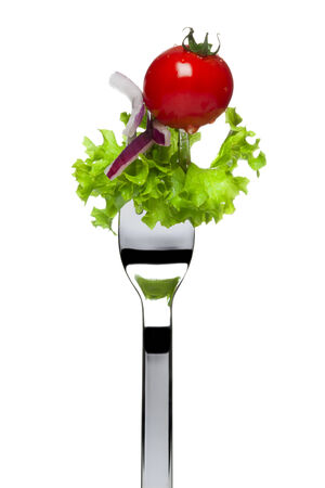 tine: fresh salad consisting of lollo bionda lettuce, red onion and cherry tomato sticked on fork, isolated on white