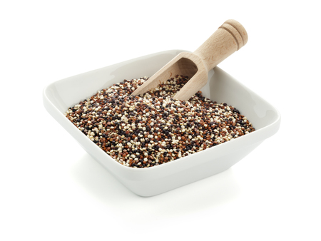 square bowl filled with quinoa seeds, wooden shovel inside, isolated on white